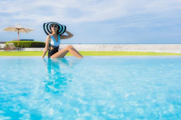 Portret pięknych młodych azjatykcich kobiet szczęśliwy uśmiech relaksuje wokoło pływackiego basenu