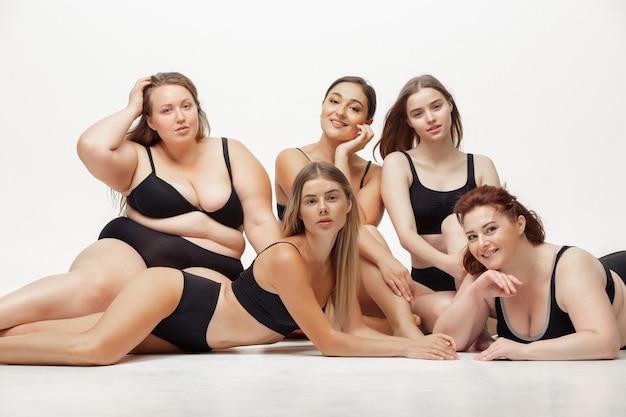 Portret pięknych młodych kobiet o różnych kształtach pozowanie na białym tle. szczęśliwe modelki. pojęcie pozytywnego ciała, piękna, mody, stylu, feminizmu. różnorodność.