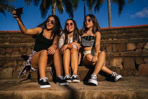 Portret pięknych przyjaciół z okularami przeciwsłonecznymi przy selfie