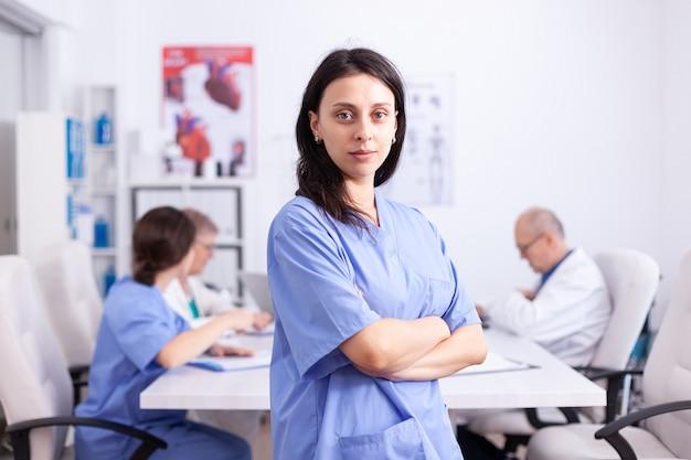 Portret pielęgniarki medycznej uśmiechający się, patrząc na kamery w sali konferencyjnej szpitala. przyjazny lekarz w sali konferencyjnej kliniki, szlafrok, specjalista.