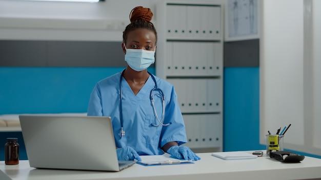 Portret pielęgniarki siedzącej przy biurku z laptopem i dokumentami podczas noszenia munduru, rękawiczek i maski na twarz w placówce medycznej. asystent patrzący w kamerę z butelką tabletek na stole
