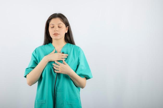 Portret pielęgniarki sprawdza jej serce stetoskopem na białym.