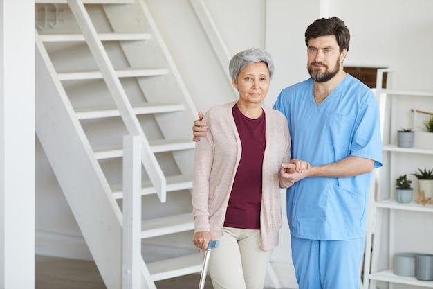 Portret pielęgniarki w mundurze trzymając rękę starszej kobiety i patrząc na kamery, stojąc w domu