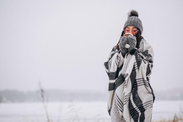 Portret pije kawę w zima parku młoda kobieta