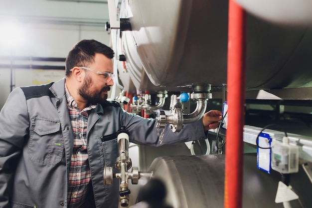 Portret piwowara, który robi piwo w swoim miejscu pracy w warzelni.