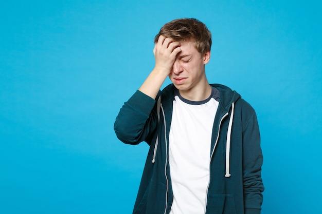Portret płacz niezadowolony młody człowiek w ubranie, trzymając zamknięte oczy, kładąc rękę na głowie na białym tle na niebieskiej ścianie. koncepcja życia szczere emocje ludzi.