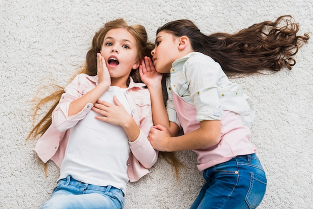 Portret plotkarki opowiadającej sekret w uchu swojej przyjaciółce leżącej na dywanie