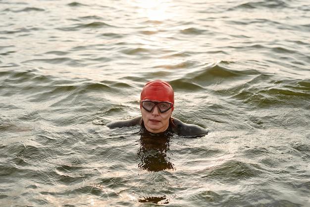 Portret pływaczki w okularach pływackich patrzącej na kamerę podczas pływania w jeziorze