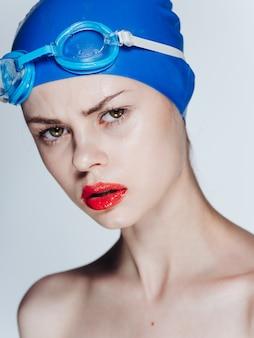 Portret pływaka w niebieskiej czapce i okularach z jasnymi czerwonymi dębami makijaż