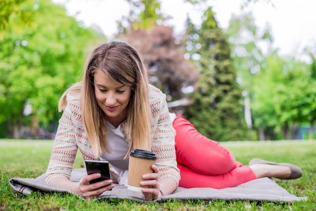 Portret po stronie kobieta laughing leżącego w trawy na zewnątrz z telefonu komórkowego. dziewczyna przy użyciu inteligentnego telefonu na trawie parku z zielonym tłem