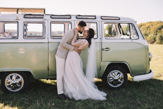 Portret pocałunków i uścisków namiętnej pary w pobliżu samochodu retro