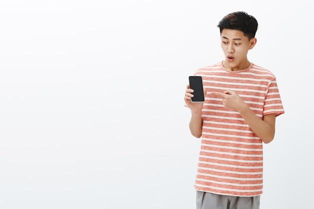 Portret pod wrażeniem i zaskoczeniem podekscytowanym młodym atrakcyjnym chińczykiem w pasiastej koszulce z otwartymi ustami z zainteresowania i emocji, trzymając smartfon wskazujący i patrząc na ekran telefonu komórkowego zafascynowany
