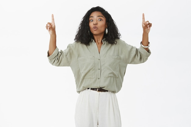 Portret pod wrażeniem zaskoczony i rozbawiony african american kobieta w stylowej koszuli i spodniach, podnosząc ręce