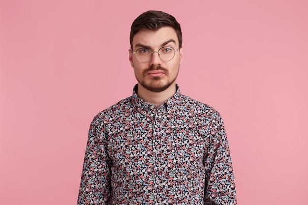 Portret podejrzanego, zamyślonego młodego brodatego mężczyzny w okularach w kolorowej koszuli, myślący o czymś, z jedną brwią uniesioną pytająco, z poważnym i zdziwionym wyrazem twarzy