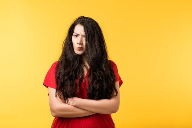 Portret podejrzanej emocjonalnej brunetki z założonymi rękoma, zaniepokojony, nieufny wyraz twarzy.