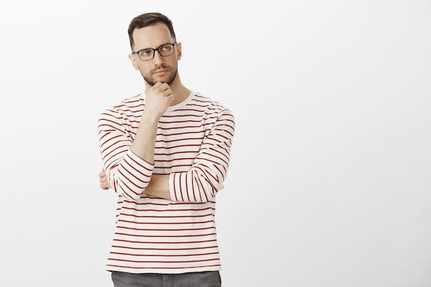 Portret podejrzanie myślącego atrakcyjnego mężczyzny w pasiastych ubraniach i okularach, patrzącego na bok i marszczącego brwi, dotykającego włosia, zaniepokojonego problematyczną decyzją