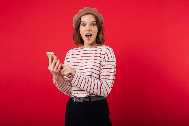 Portret podekscytowana kobieta nosi beret trzymając telefon komórkowy
