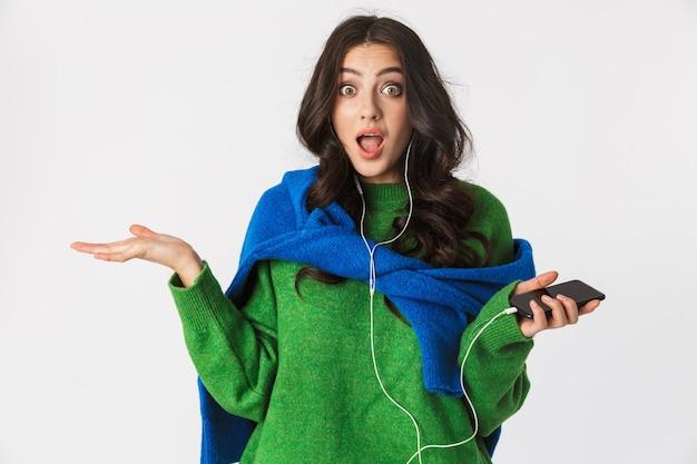 Portret podekscytowana kobieta o ciemnych włosach, noszenie słuchawek i trzymając telefon komórkowy, podczas gdy na białym tle