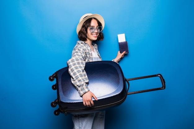 Portret podekscytowana młoda kobieta ubrana w letnie ubrania, trzymając paszport z biletami lotniczymi, stojąc z walizką na białym tle