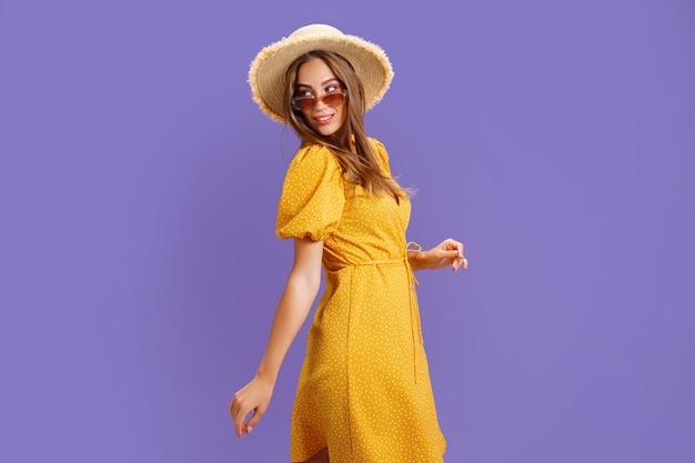 Portret podekscytowana młoda kobieta w żółtej sukience letni kapelusz okulary pozuje na białym tle na pastelowe wiolon...