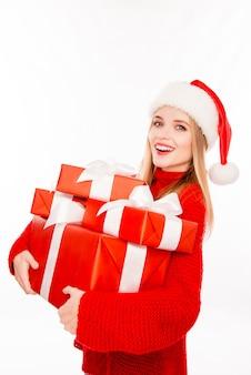 Portret podekscytowana szczęśliwa dziewczyna w santa hat trzyma prezenty na nowy rok