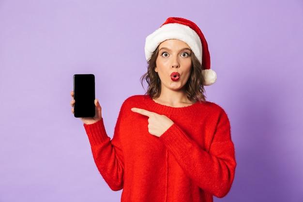 Portret podekscytowana szczęśliwa młoda kobieta ubrana w boże narodzenie kapelusz na białym tle nad fioletową ścianą pokazujący wyświetlacz telefonu komórkowego.