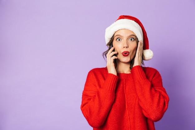 Portret podekscytowana szczęśliwa młoda kobieta ubrana w boże narodzenie kapelusz na białym tle nad fioletową ścianą rozmawia przez telefon komórkowy.