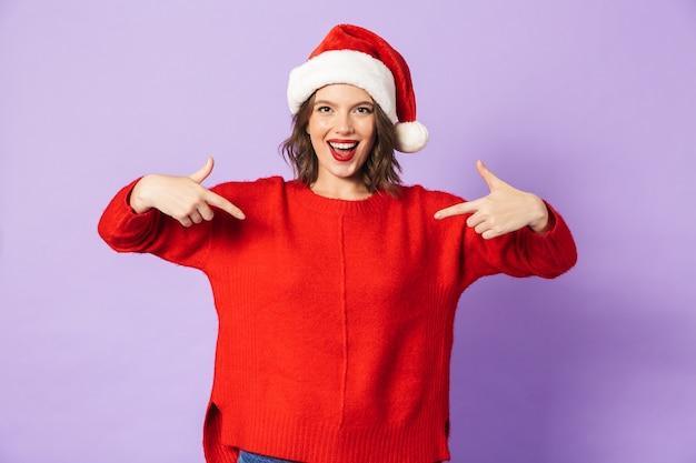 Portret podekscytowana szczęśliwa młoda kobieta ubrana w boże narodzenie kapelusz na białym tle nad wskazując fioletową ścianą.