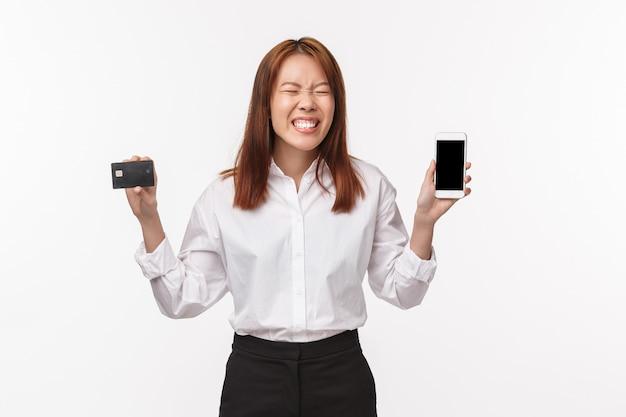 Portret podekscytowana, szczęśliwa uśmiechnięta azjatka w karcie kredytowej, pokazująca wyświetlacz telefonu komórkowego, zamknij oczy i śmiejąca się, gdy wreszcie zamawia to, czego chciała, traktuje siebie, internet i koncepcję finansów