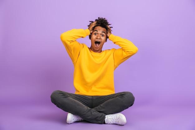 Portret podekscytowanego african american chłopca krzyczącego i chwytającego głowę siedząc na podłodze ze skrzyżowanymi nogami, na białym tle na fioletowym tle