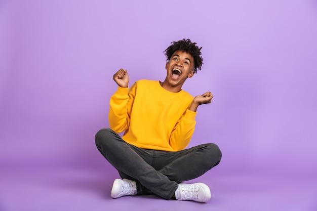 Portret podekscytowanego afroamerykańskiego chłopca krzyczącego i patrzącego na bok siedząc na podłodze ze skrzyżowanymi nogami, na białym tle nad fioletowym tłem