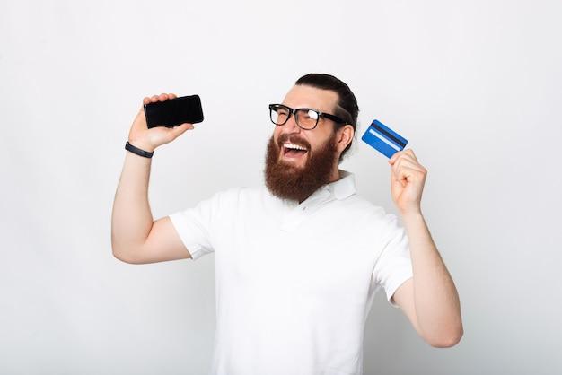 Portret podekscytowanego brodatego mężczyzny trzymającego smartfona i niebieską kartę kredytową
