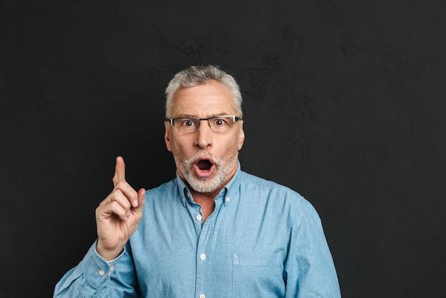 Portret podekscytowanego emerytowanego mężczyzny w wieku 60 lat z siwymi włosami i brodą w koszuli, krzyczący ze zdziwienia, ma pomysł i wskazuje palec wskazujący w górę na copyspace, odizolowany na czarnej ścianie