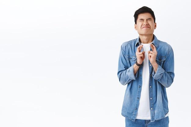 Portret podekscytowanego i przytłoczonego młodego azjatyckiego studenta płci męskiej potrzebuje dobrego wyniku w teście źle, zamknij oczy, stojąc intensywnie, czekając na ważne wyniki, nerwowo krzyżując palce, modląc się