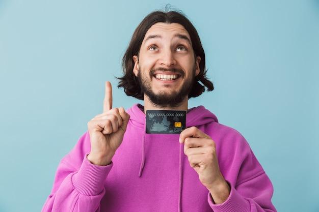 Portret podekscytowanego młodego brodatego mężczyzny w zwykłych ubraniach, stojącego na białym tle nad ścianą, pokazującego kartę kredytową i wskazującego w górę