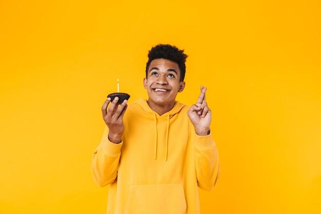 Portret podekscytowanego młodego nastolatka stojącego na białym tle nad żółtą ścianą, trzymającego urodzinową babeczkę ze świecą, trzymającego skrzyżowane palce