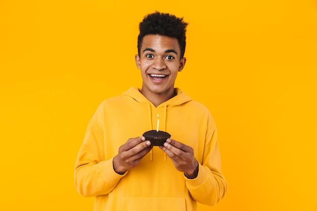 Portret podekscytowanego młodego nastolatka stojącego na białym tle nad żółtą ścianą, trzymającego urodzinową babeczkę ze świecą