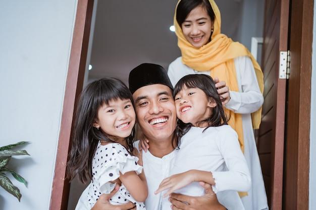 Portret podekscytowanego ojca przytulającego i obejmującego swoje dzieci podczas wspólnej uroczystości eid mubarak