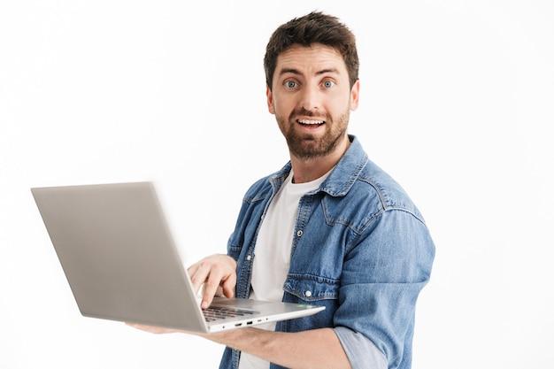 Portret podekscytowanego, przystojnego brodatego mężczyzny noszącego zwykłe ubrania, stojącego na białym tle, korzystającego z laptopa
