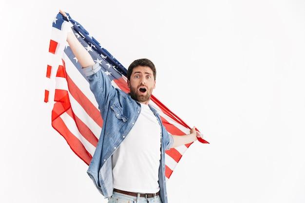 Portret podekscytowanego przystojnego brodatego mężczyzny noszącego zwykłe ubrania stojącego na białym tle, noszącego amerykańską flagę