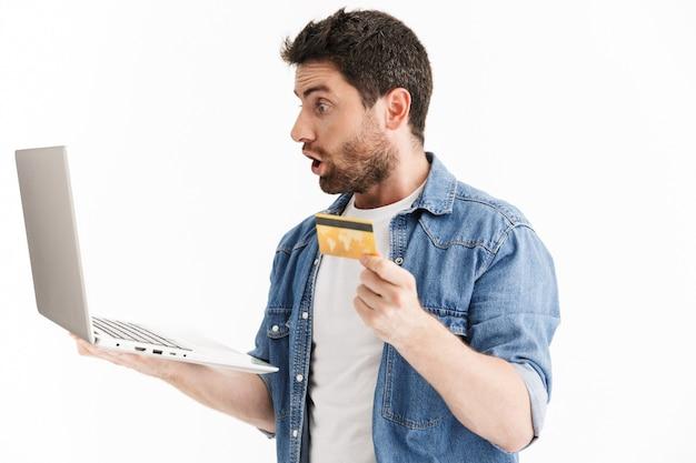 Portret podekscytowanego, przystojnego brodatego mężczyzny noszącego zwykłe ubrania, stojącego na białym tle, używającego laptopa, pokazującego kartę kredytową