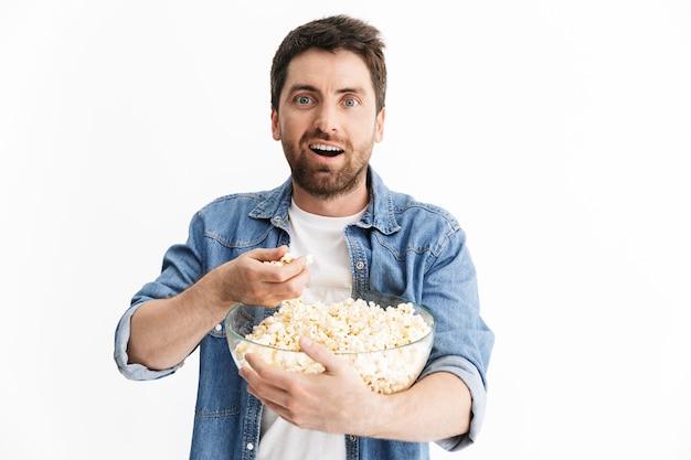 Portret podekscytowanego, przystojnego brodatego mężczyzny w zwykłych ubraniach, stojącego na białym tle, oglądającego film, jedzącego popcorn