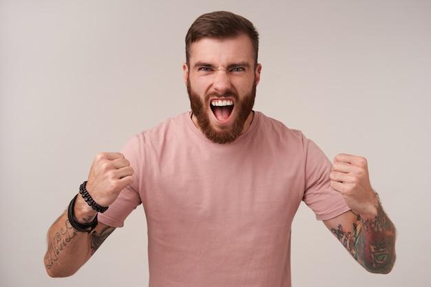 Portret podekscytowanego przystojnego brodatego mężczyzny z tatuażami, ubranego w beżową koszulkę i modne dodatki, krzyczącego głośno i składającego ręce w pięści stojąc na białym