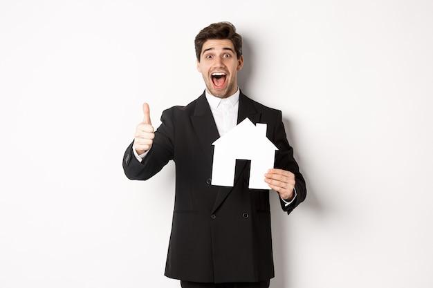 Portret podekscytowanego przystojnego mężczyzny szukającego domu, pokazujący dom i kciuk w górę, polecający agencję nieruchomości, stojący na białym tle.