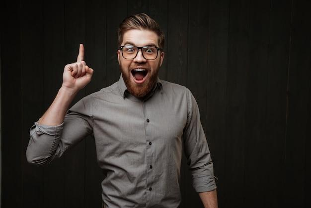 Portret podekscytowanego, szczęśliwego brodatego mężczyzny w okularach wskazujących palcem w górę na białym tle na czarnej drewnianej powierzchni