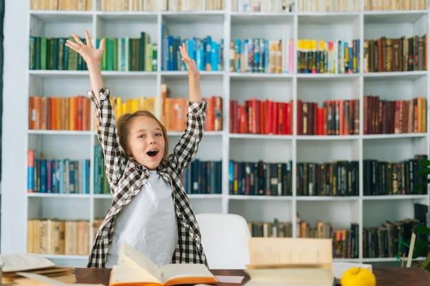 Portret podekscytowanego, szczęśliwego dziecka w szkole podstawowej, podniesionych rąk, aby uczcić sukces