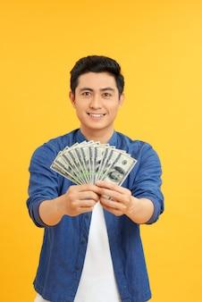 Portret podekscytowanego, zdziwionego, zdziwionego, zdumionego, wesołego, radującego się menedżera pokazującego wiele banknotów odizolowanych na żółtym tle