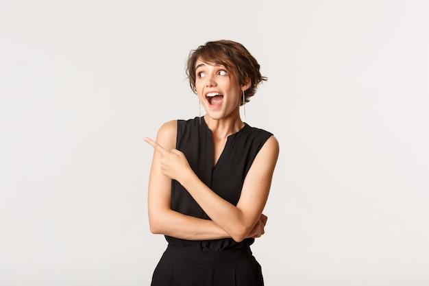 Portret podekscytowanej atrakcyjnej kobiety z otwartymi ustami zdumiony, wskazując i patrząc w lewy górny róg, biały.