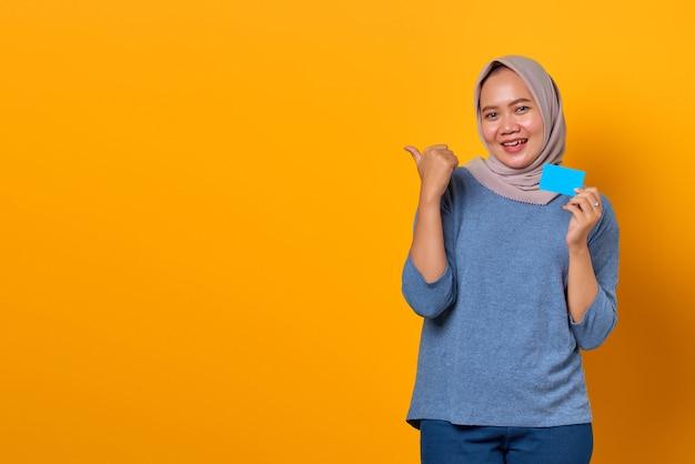 Portret podekscytowanej azjatki trzymającej kartę kredytową i wskazującego palcem na pustą przestrzeń