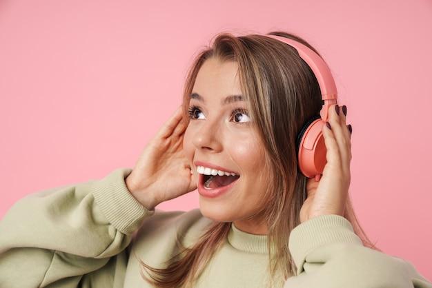 Portret podekscytowanej blondynki używającej słuchawek i patrzącej w górę odizolowanej nad różową ścianą